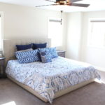 master bedroom with white walls white and blue bedset
