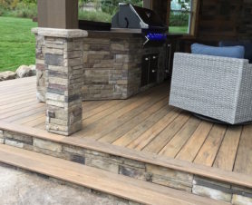 outdoor grill on wooden deck with brick